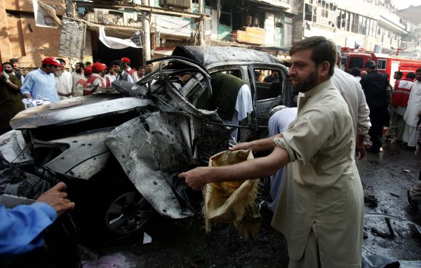 Security officers collect evidence from the site of a suicide bomb attack in Peshawar